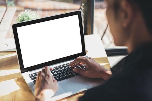 Young man working on his laptop with blank copy space screen for your advertising text message in office, Back view of business man hands busy using laptop at office desk